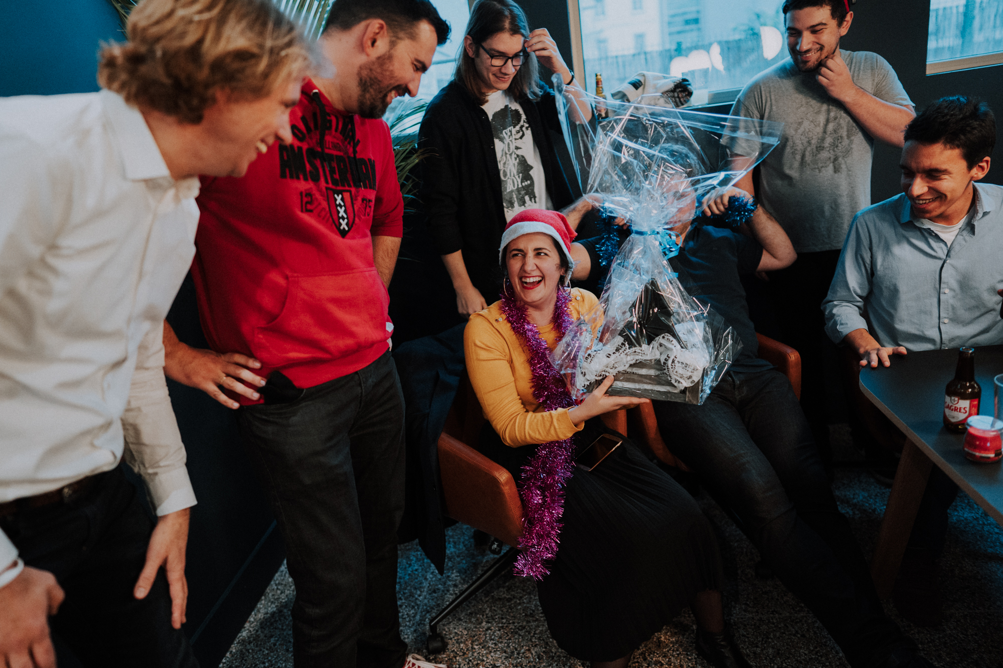 At Nmbrs, we're a tight-knit family. In the image, there is Rita, our Recruitment Lead, surrounded by her team from a game we did during the Christmas party of 2019 in Lisbon. They're laughing and celebrating having won the game.