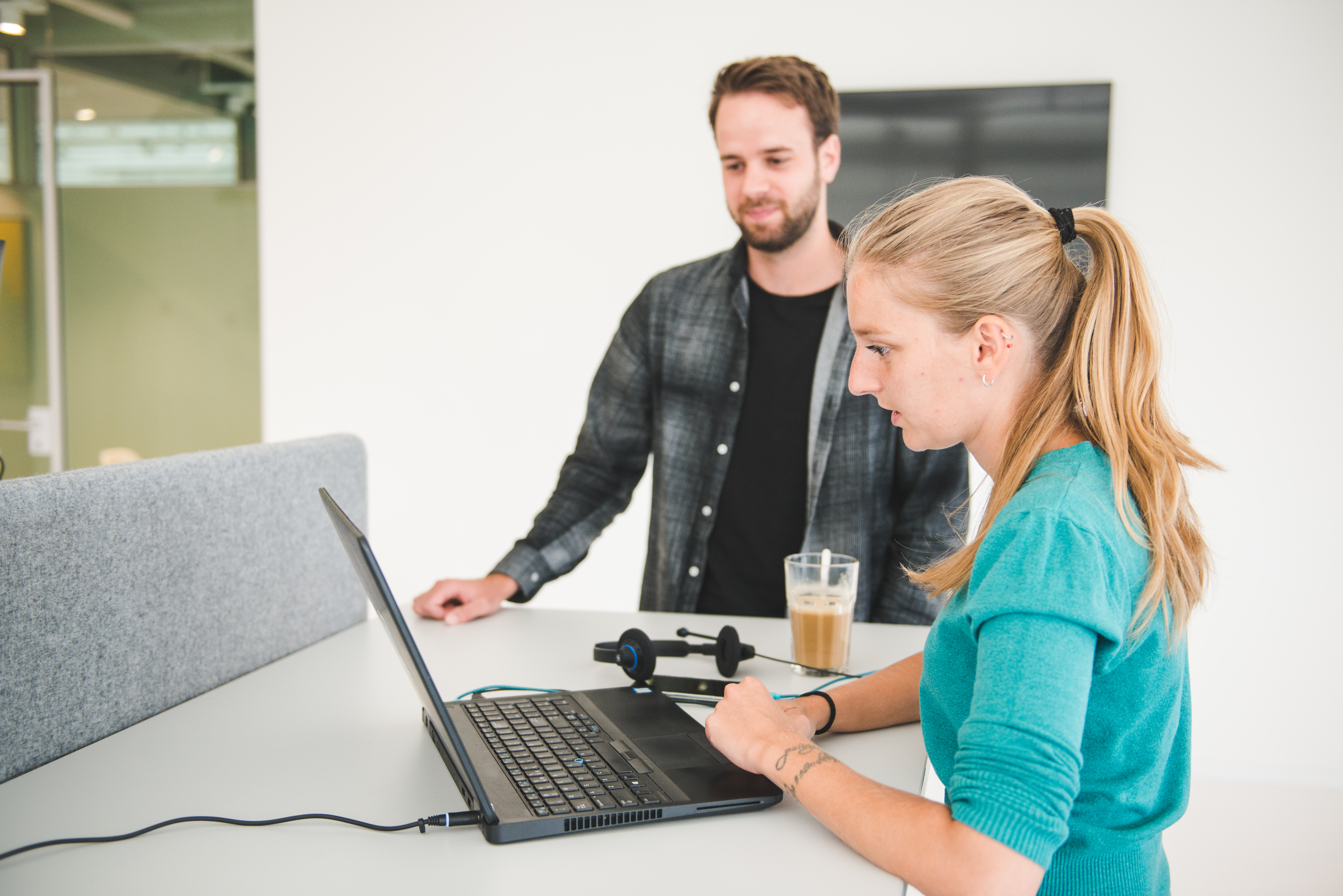 At Nmbrs, we work with multi-function teams. Our AI developer is showing something on the computer to our Content Marketeer.
